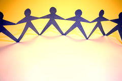 Unity. A row of blue paper men holding hands and standing against an organge background Royalty Free Stock Image