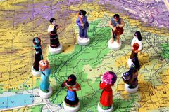 Unity. Porcelain figurines on map, representing people of the world Stock Image