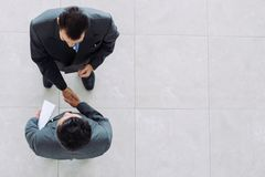 Unity. Business partners shaking hands as a symbol of unity, view from the top Royalty Free Stock Photography