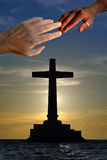 Unity in Christ. Large concrete cross silhouette over a marine sunset with a Caucasian and a black hand touching on top in unity Stock Photos
