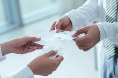 Unity and collaboration. Business colleagues assembling puzzle as a symbol of unity and collaboration, selective focus royalty free stock image
