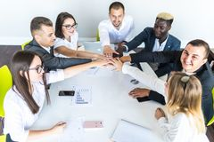 Unity concept. Close-up of multi ethnic people holding hands together while sitting around the desk royalty free stock images