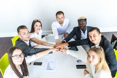 Unity concept. Close-up of multi ethnic people holding hands together while sitting around the desk stock images