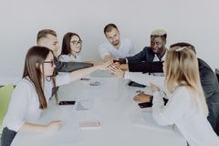Unity concept. Close-up of multi ethnic people holding hands together while sitting around the desk royalty free stock photos