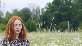 Unity with nature, young woman sits with closed eyes meditating, inner peace. Stock footage stock video footage