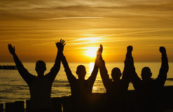 Unity and strength. Men silhouette with the sunset in the bottom Royalty Free Stock Photos