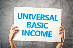 Universal basic income concept. With hands holding banner Royalty Free Stock Image