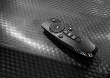 Universal remote control isolated on black texture background. Modern TV remote controller Stock Images