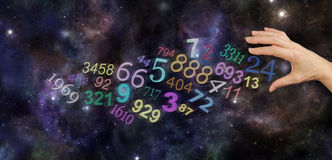 The Universal Significance of Numbers. Female hand about to take number 24 among a group of scattered multicolored transparent numbers on a wide deep space Royalty Free Stock Images