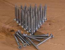 Universal silver screws with a triangle pointing upwards.  Stock Image