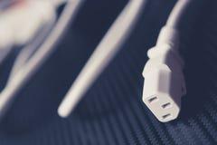 Universalstromkabel auf Kohlenstoffhintergrund-Nahaufnahmefoto weiß Stockfoto