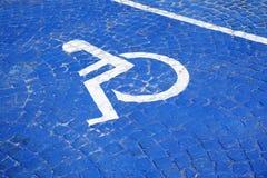 Universalzeichen für Handikap-Parklücke Rollstuhl mit Hinweiszeichen auf Bodenhintergrund für Sperrung stockfotografie