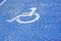 Universalzeichen für Handikap-Parklücke Rollstuhl mit Hinweiszeichen auf Bodenhintergrund für Sperrung lizenzfreies stockbild