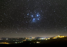 The Universe above city lights. The Pleiades. The Pleiades star cluster shines over the lights of a mountain village Stock Photos