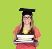 Universidad con el casquillo de la graduación y muchos libros Imagenes de archivo