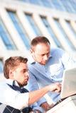 Universidad de dos jóvenes usando la computadora portátil Foto de archivo libre de regalías
