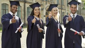 A universidade gradua-se na insígnia real acadêmico que guarda os diplomas, pondo os polegares-acima vídeos de arquivo