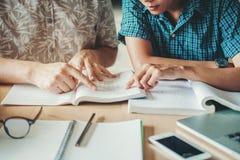 Università che studia gli amici che studiano e che leggono libri in clas fotografie stock libere da diritti