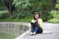 Università o studente di college femminile, messo da un lago in un parco Immagini Stock