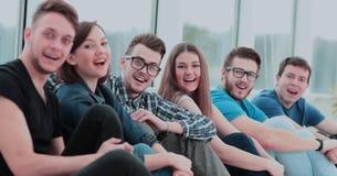 Université par groupe d'étudiants s'asseyant sur le plancher dans le gymnase a Photo stock