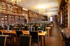 Universitair Bibliotheekbinnenland met vele studentenbureaus en boekenrek met oude boeken stock foto