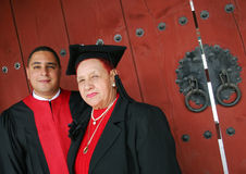 Universitaire gediplomeerde in robes met zijn grootmoeder stock foto's