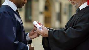 Universitaire kanselier die diploma geven aan gediplomeerde student, succesvolle toekomst royalty-vrije stock foto