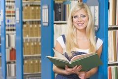 Universitaire student die in bibliotheek bestudeert Stock Foto
