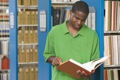 Universitaire student die in bibliotheek werkt Stock Foto's
