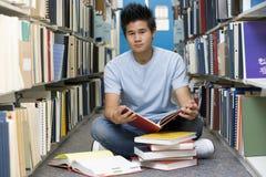 Universitaire student die in bibliotheek werkt Stock Foto