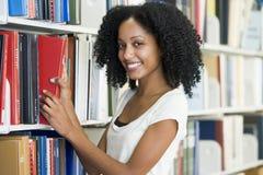 Universitaire student die boek in bibliotheek selecteert Stock Foto