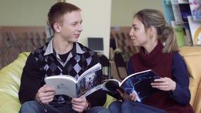 Universitaire studenten die in bibliotheek artikelen van hun boeken bespreken stock footage