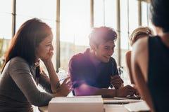 Universitaire studenten die bij laptop en het glimlachen werken royalty-vrije stock afbeelding