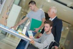 Universitaire studenten die brochures lezen bij ingang Royalty-vrije Stock Fotografie