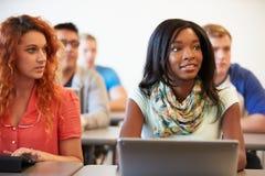 Universitaire Studenten die Digitale Tablet en Laptop in Klasse met behulp van royalty-vrije stock fotografie