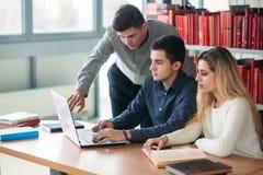 Universitaire studenten die samen bij lijst met boeken en laptop zitten Gelukkige jongeren die groepsstudie in bibliotheek doen stock afbeelding
