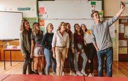 Universitaire studenten die selfie met leraar nemen stock afbeelding