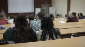 Universitaire studenten en professoren in een universiteitsklaslokaal die worden onderwezen stock footage
