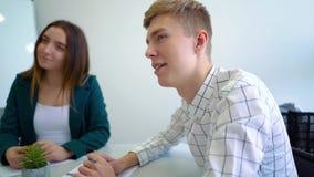 Universiteits mannelijke en vrouwelijke studenten die groepswerkpraktijk hebben bij lijst stock video
