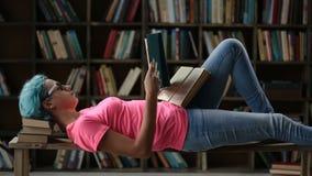 Universiteits vrouwelijke student die hard in bibliotheek bestuderen stock video