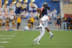 2014 Universiteitsvoetbal - het springen vangst Stock Foto's
