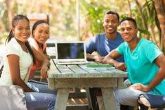 Universiteitsvrienden die in openlucht zitten royalty-vrije stock afbeeldingen