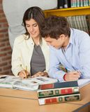 Universiteitsvrienden die samen bij Bibliotheek bestuderen Stock Foto