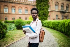 Universitetsområdeliv Kvinnlig högskolestudent för ung attraktiv afrikansk amerikan på universitetsområde royaltyfria bilder