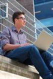 Universitetsstudent som utomhus arbetar på bärbara datorn Arkivbild
