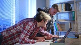 Universitetsstudenter som använder bärbara datorn i ett arkiv arkivfilmer
