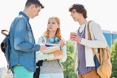 Universitetsstudenter som samtalar på universitetsområdet arkivbilder