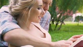 Universitetsstudentläseboken och att kyssa in parkerar, romantisk fritid, förälskelse lager videofilmer
