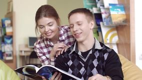 University boy discussing an article from a book with pretty university girl stock footage
