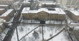 University building with flying snow and moving people. Cityscapes aerial survey using quadcopter stock video footage